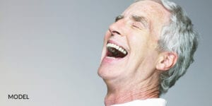 Older Patient With Dental Implants Opening Mouth Widely While Laughing